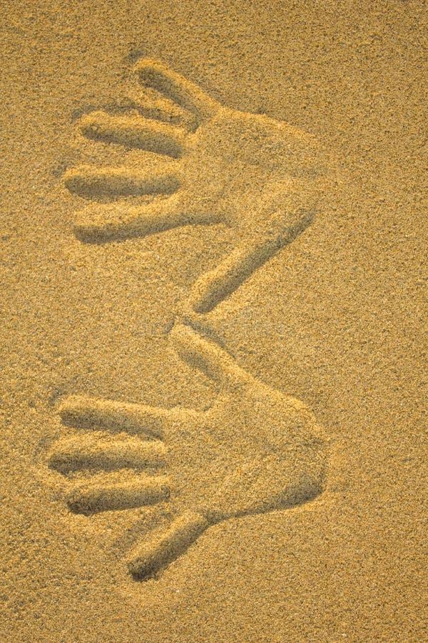 Direito e impressão da mão esquerda no fim amarelo da areia acima imagem de stock