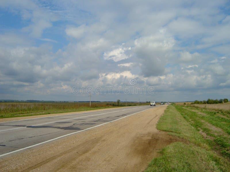 Direkt asfaltväg till och med bygden under himlen, som molnen svävar på arkivfoto