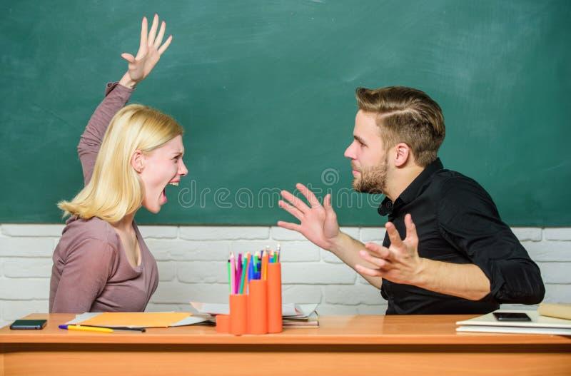 Direkt opposition Par som argumenterar i klassrum Ilsken kvinna som går till mannen med hennes nävar Läraren och läraren är på arkivfoton