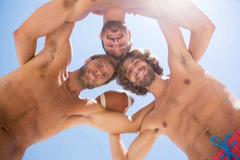 Direkt unter Porträt von den männlichen die Köpfe zusammensteckenden Freunden beim Spielen des amerikanischen Fußballs stockbild