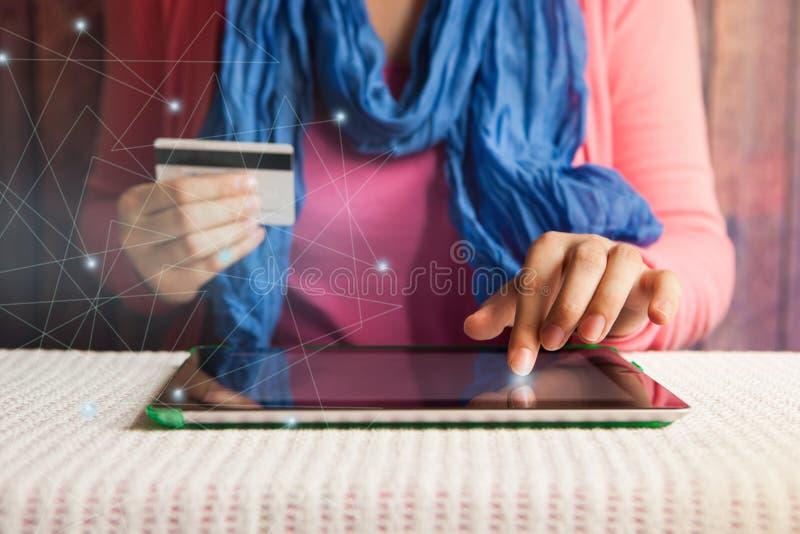 Direktanslutet shoppa härlig kvinna med kreditkorten i handen som betalar eller bokar i internet arkivfoton