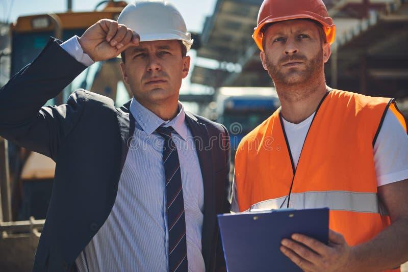 Direktor mit Arbeitskraft finden an der Baustelle stockbild