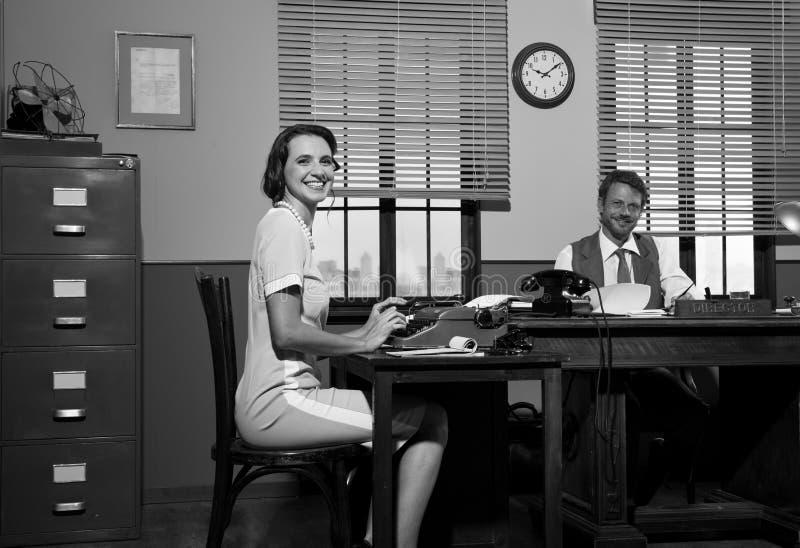 Diretor e secretário de sorriso no trabalho fotos de stock