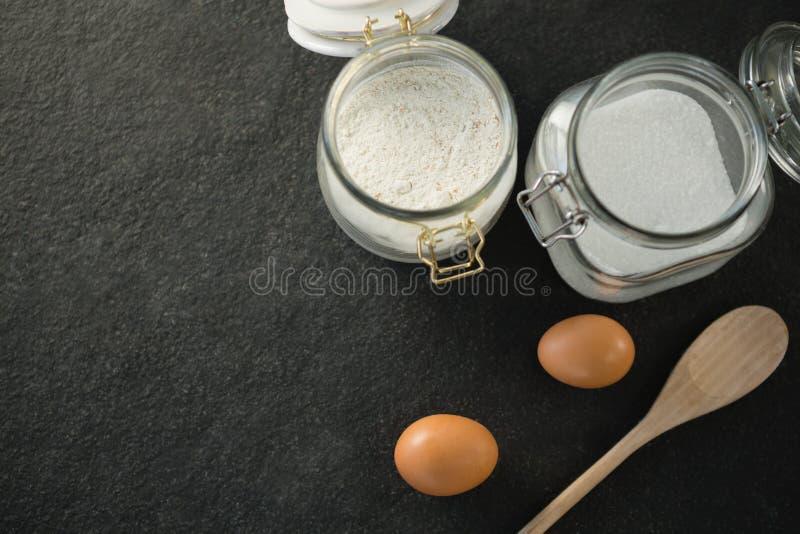 Direttamente sopra il colpo del cucchiaio di legno dalle uova con zucchero e farina in barattolo fotografia stock libera da diritti