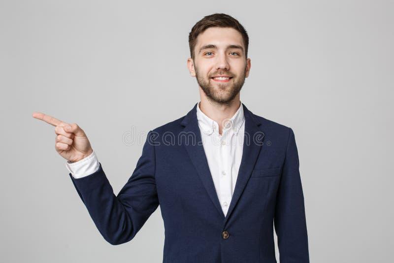 Direttiva indicante del giovane riuscito uomo d'affari con il dito sopra fondo grigio scuro Copi lo spazio fotografia stock libera da diritti