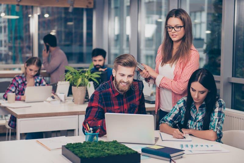 Direttore aziendale che controlla compito finanziario dei suoi colleghi I colleghi intelligenti abili astuti che discutono il nuo fotografia stock