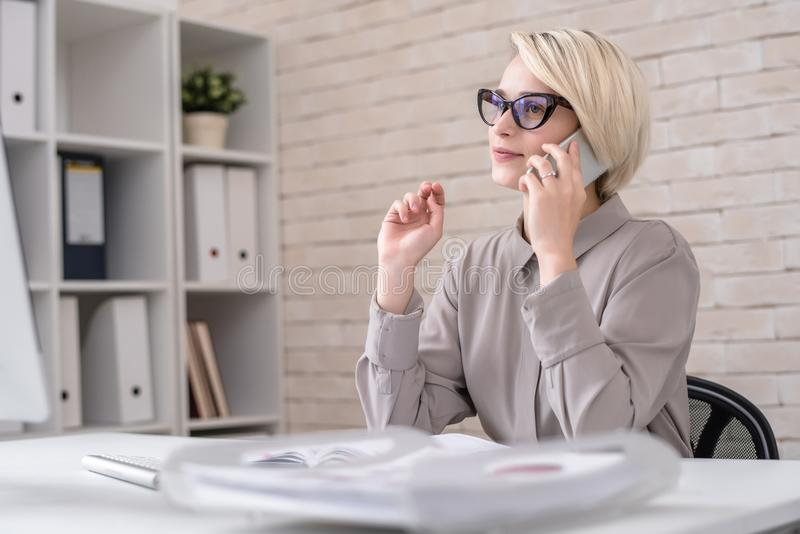 Direttore di marketing Talking al cliente dal telefono immagine stock