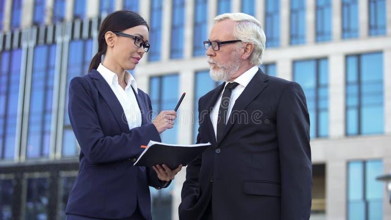 Direttore femminile che dà penna all'investitore anziano, contratto di firma, cooperazione immagini stock libere da diritti