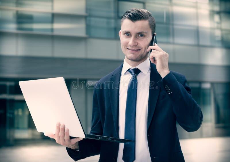 Direttore sta stando con il computer portatile vicino all'ufficio fotografie stock libere da diritti