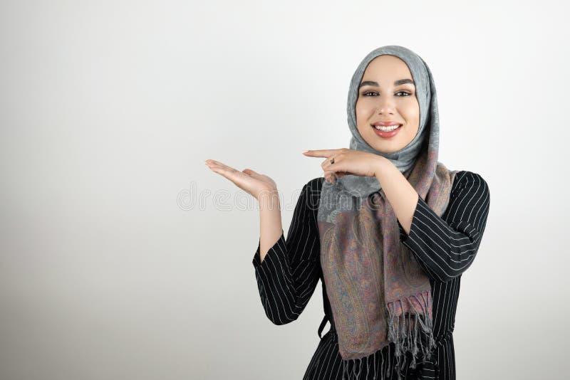 Direzione d'uso di rappresentazione del foulard del hijab del turbante del giovane studente musulmano attraente con il suo dito v fotografia stock