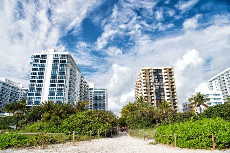 Direzione del percorso dalla spiaggia tropicale alle costruzioni di appartamento immagini stock