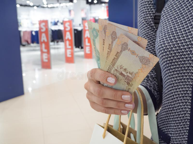 Dirhams árabes em uma mão do ` s da mulher no fundo das vendas na loja Sacos de compras em uma mão do ` s da mulher fotos de stock