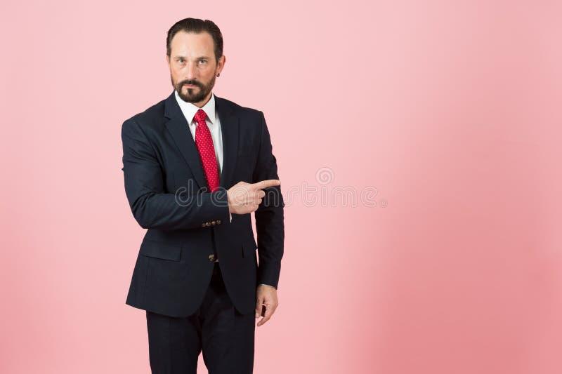Dirigeant barbu indiquant par le doigt la gauche Expositions de vendeur à placer à la main Publicité de directeur dans le costume photographie stock