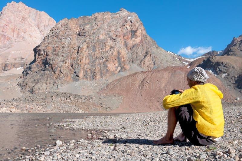 Dirigen al hombre en las montañas cerca del lago fangoso foto de archivo