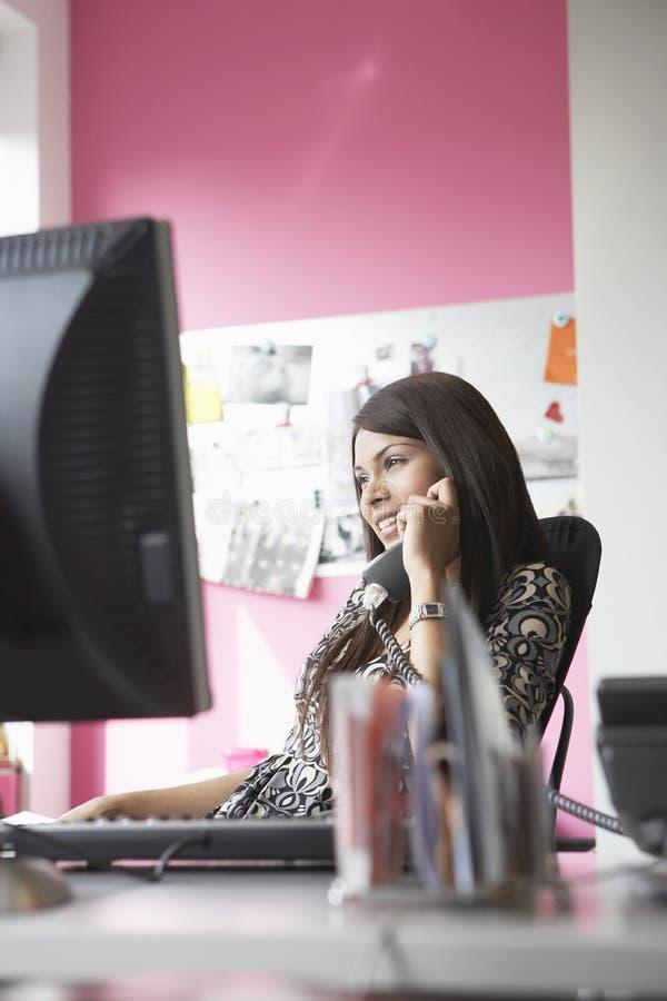 Dirigente femminile sorridente che per mezzo del telefono allo scrittorio fotografia stock