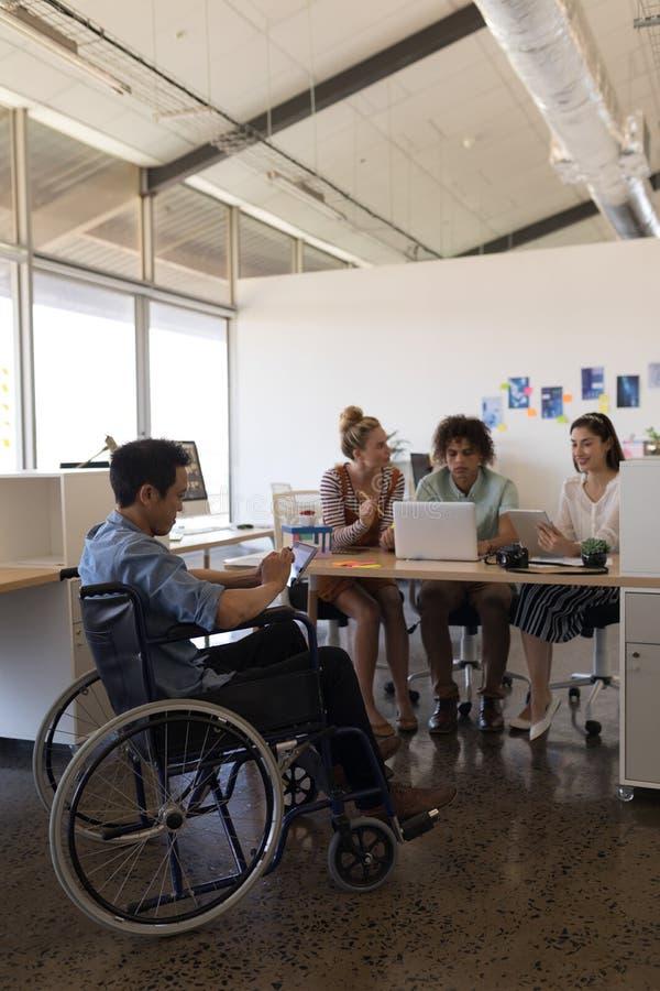 Dirigente maschio disabile che utilizza compressa digitale mentre colleghe che lavorano nei precedenti fotografie stock