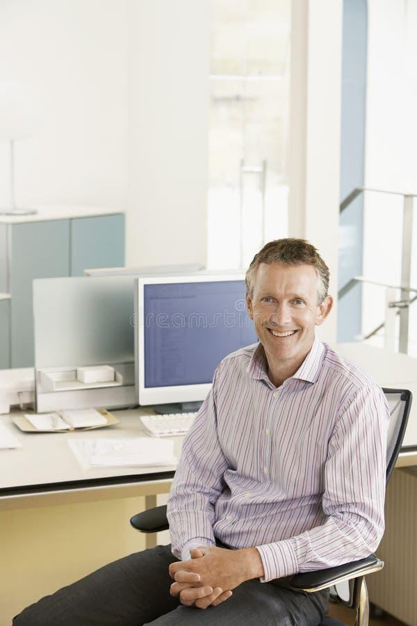 Dirigente maschio sorridente che si siede allo scrittorio immagini stock libere da diritti
