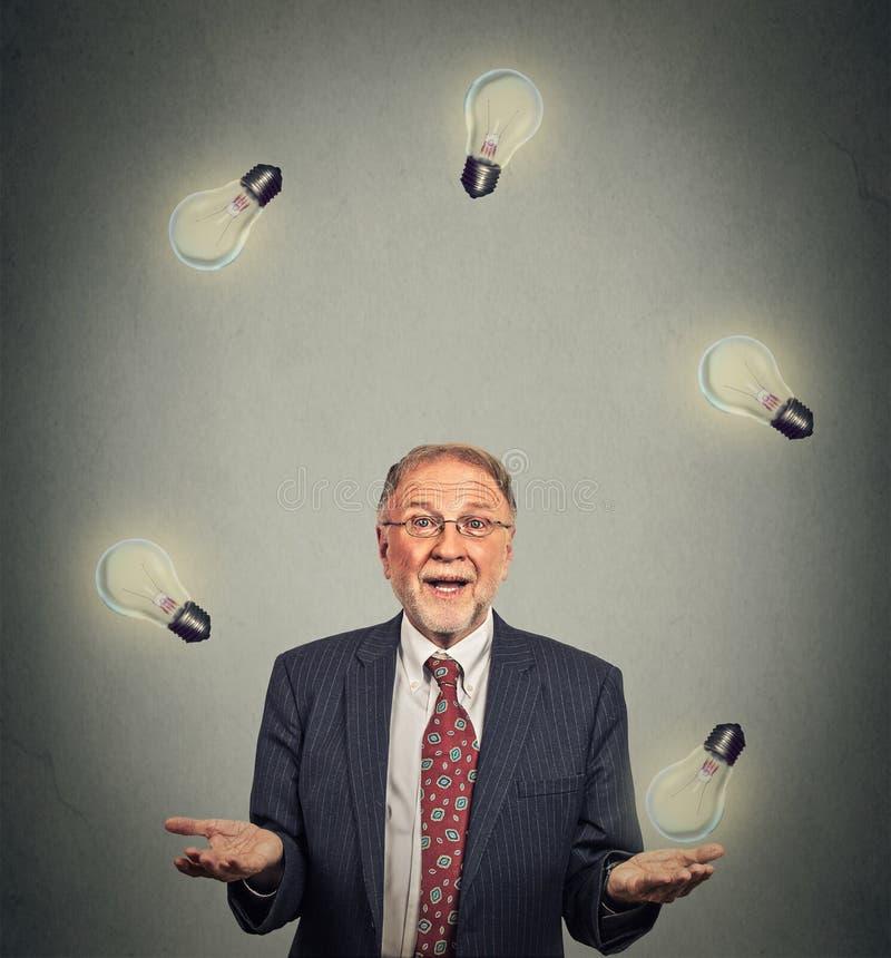 Dirigente senior dell'uomo di affari nel gioco di manipolazione del vestito con le lampadine immagini stock
