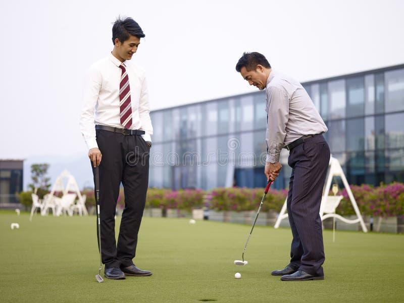 Dirigenti aziendali asiatici che giocano golf sulla corte del tetto fotografia stock