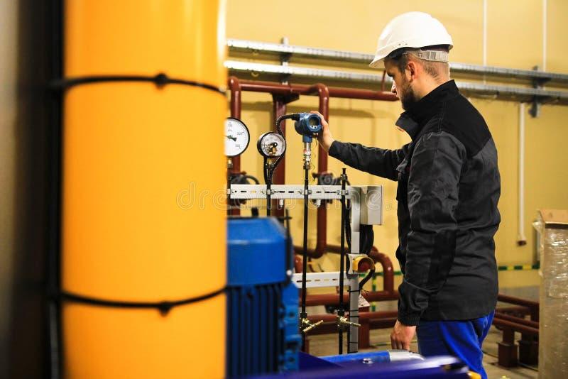 Dirigir al personal ajusta los parámetros del sensor digital de la presión en la planta industrial imágenes de archivo libres de regalías