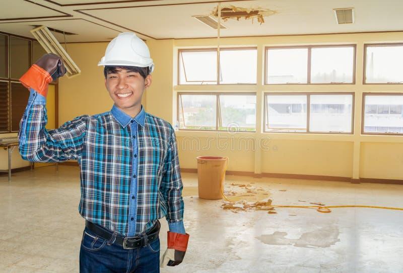 Dirigir la mano encima del brazo en escape del agua de la reparaci?n del empleo caer el edificio de oficinas interior fotografía de archivo libre de regalías