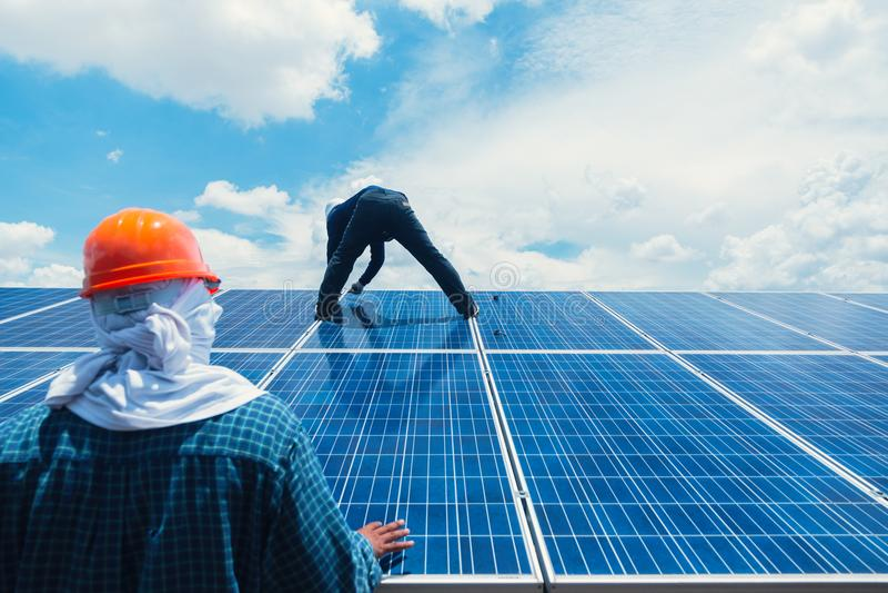 Dirija al equipo que trabaja en el panel solar del reemplazo en energía solar imágenes de archivo libres de regalías