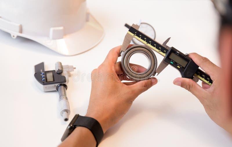Dirija al hombre que usa el calibrador a vernier que mide el transporte imagen de archivo libre de regalías