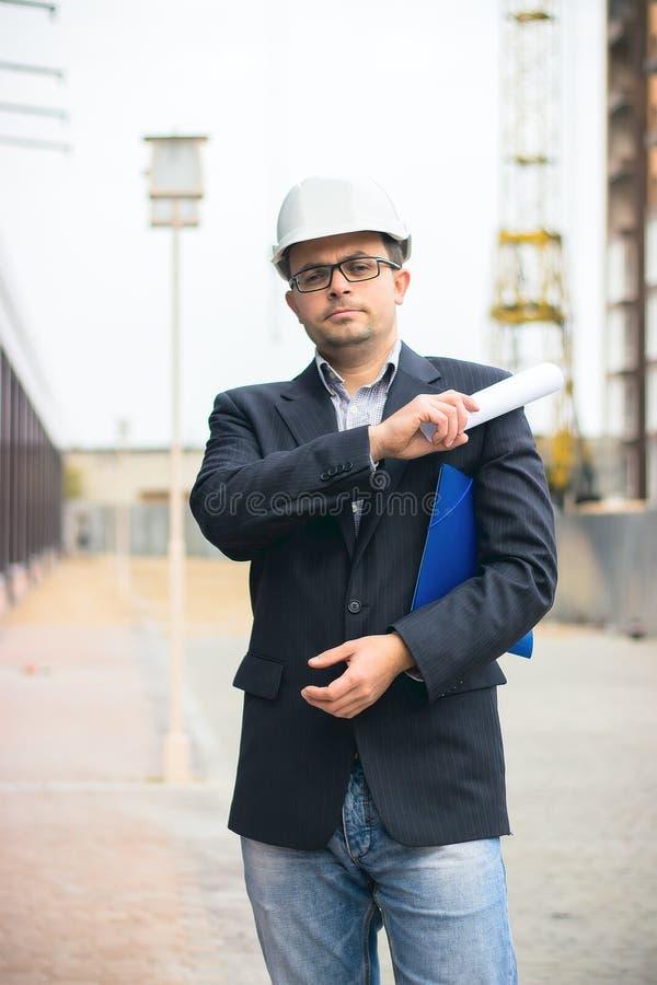 Dirija al jefe con el casco de seguridad protector que comprueba el dibujo arquitectónico en el emplazamiento de la obra imagen de archivo libre de regalías