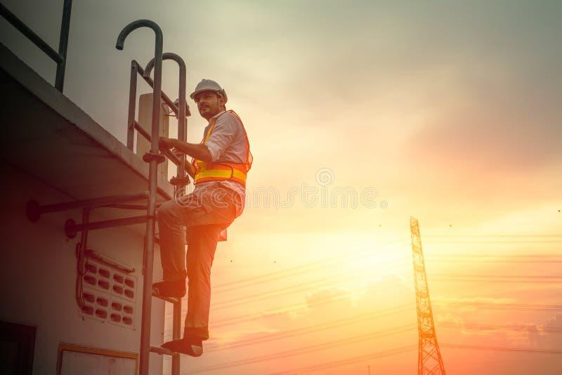 Dirija al técnico que trabaja en la escalera para fijar el cable de la electricidad imagen de archivo libre de regalías