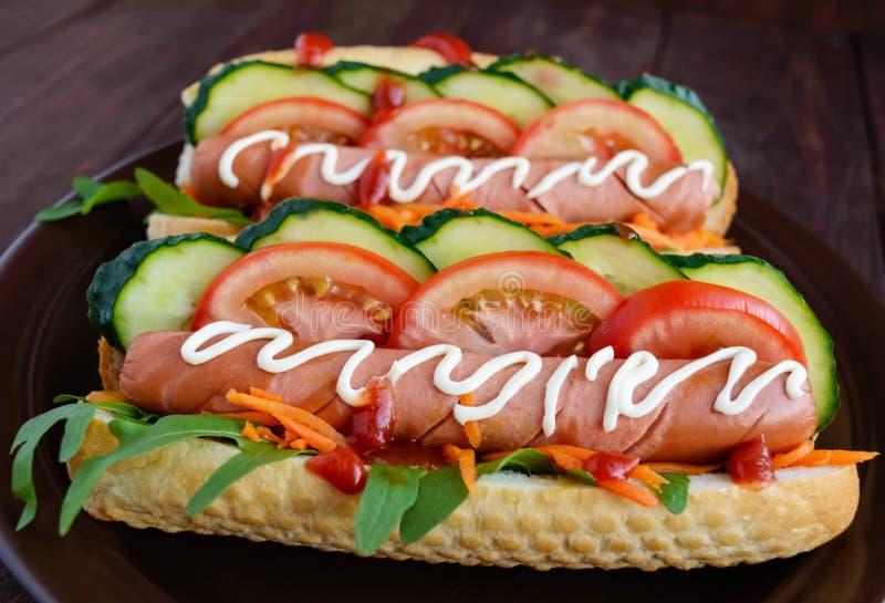 Dirija cachorros quentes feitos com vegetais, a salsicha suculenta e a rúcula no fundo de madeira foto de stock