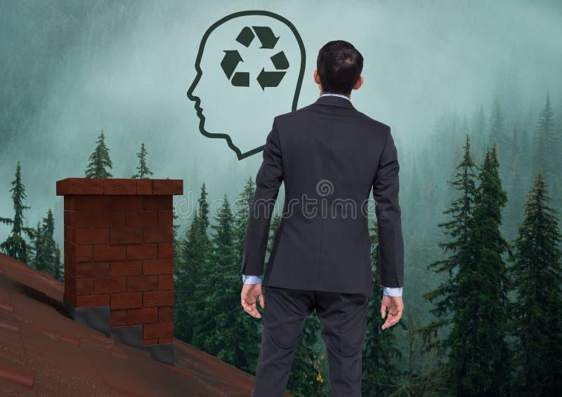 Dirija con el icono reciclable y el hombre de negocios sostenibles que se colocan en el tejado con la chimenea y el bosque brumos foto de archivo