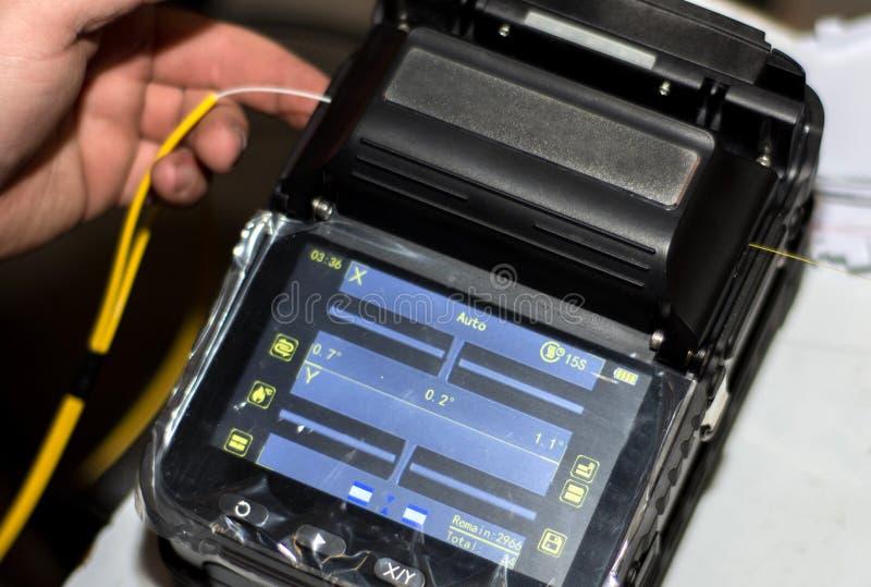 Dirija el cable de fribra óptica que empalma con la encoladora de fibra óptica de la fusión con la herramienta con la exhibición fotografía de archivo