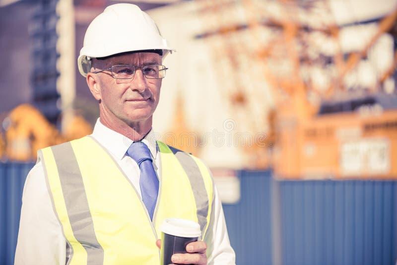 Dirija el constructor en emplazamiento de la obra en el día soleado con el café i imágenes de archivo libres de regalías