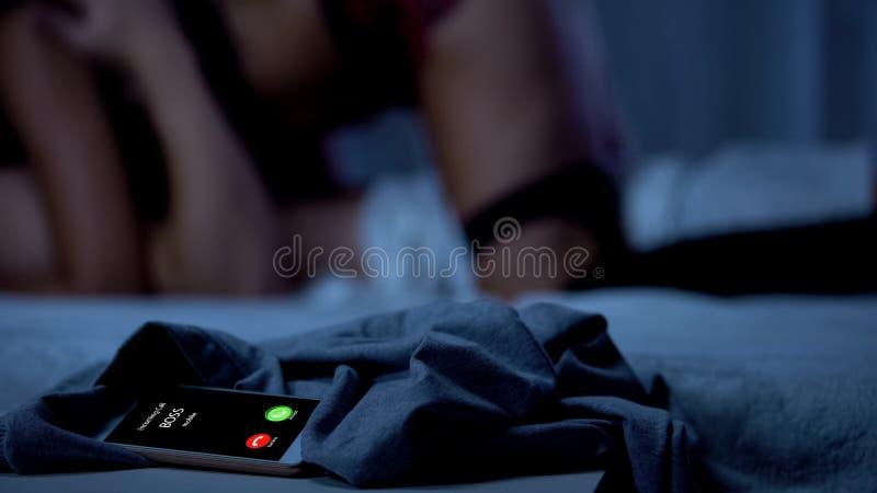 Dirija la llamada mientras que varón y amor de fabricación femenino en cama, trabajo agotador, smartphone fotografía de archivo
