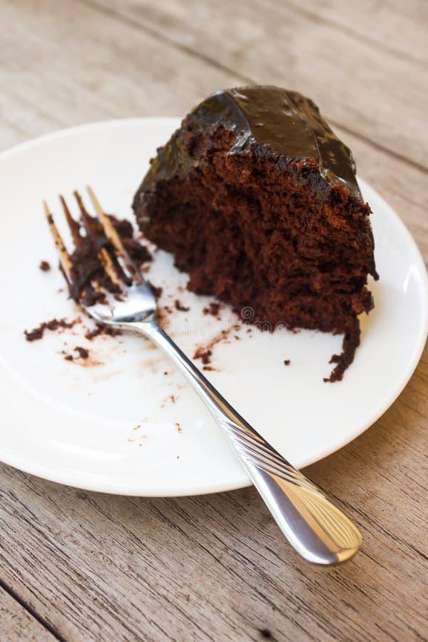 Dirija o bolo de chocolate feito com molho de chocolate na placa branca imagens de stock royalty free