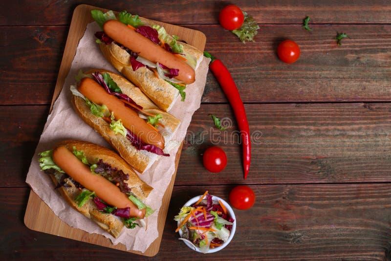 Dirija o cachorro quente feito - sanduíche com alface no fundo de madeira fotos de stock