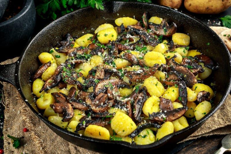 Dirija o gnocchi feito da batata com cogumelos, salsa desbastada e queijo parmesão na bandeja do ferro imagens de stock royalty free