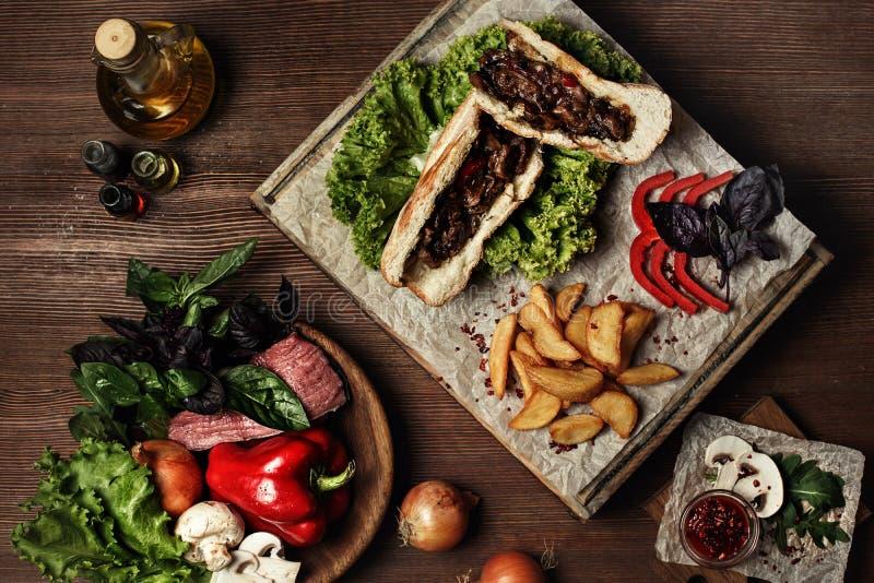 Dirija o Hamburger feito com batatas fritas, tomates de cereja imagem de stock