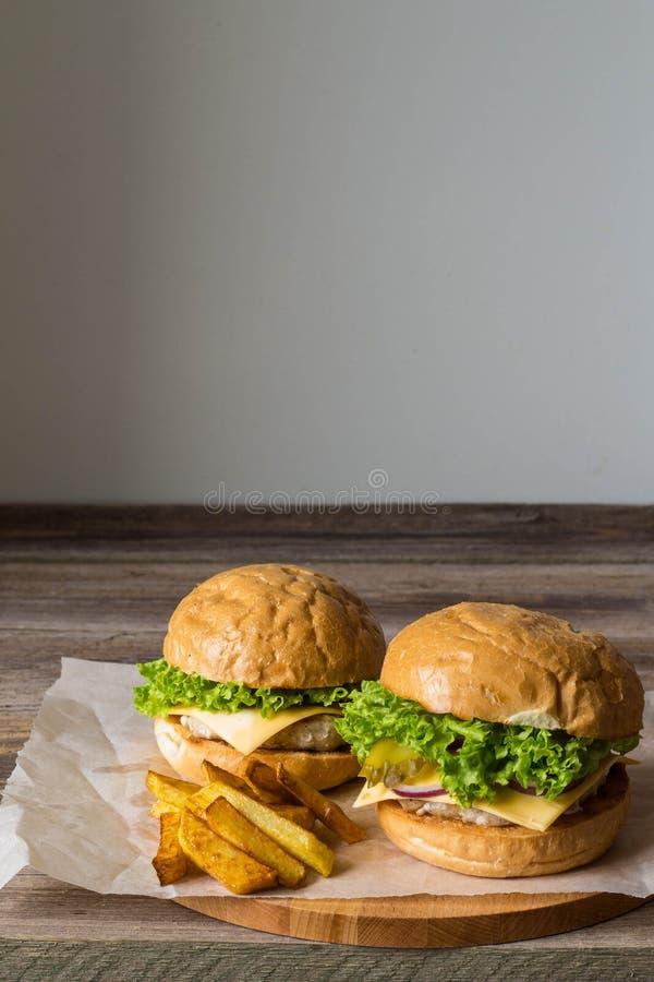 Dirija o Hamburger feito com galinha, cebola, pepino, alface e queijo na tabela de madeira com fritadas da batata foto de stock