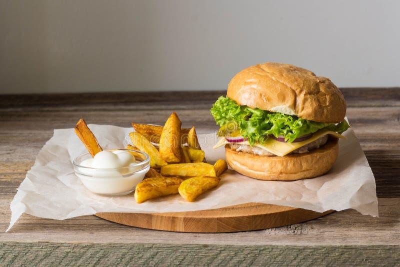 Dirija o Hamburger feito com galinha, cebola, pepino, alface e queijo na tabela de madeira com fritadas da batata imagens de stock royalty free