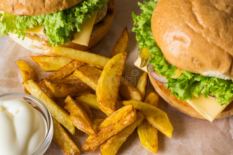 Dirija o Hamburger feito com galinha, cebola, pepino, alface e queijo na tabela de madeira com fritadas da batata fotografia de stock royalty free