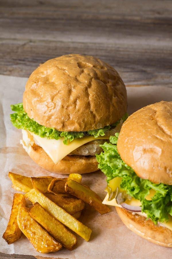 Dirija o Hamburger feito com galinha, cebola, pepino, alface e queijo na tabela de madeira com fritadas da batata imagem de stock royalty free