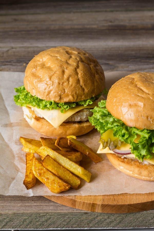 Dirija o Hamburger feito com galinha, cebola, pepino, alface e queijo na tabela de madeira com fritadas da batata fotografia de stock