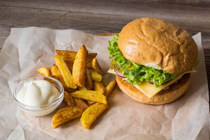 Dirija o Hamburger feito com galinha, cebola, pepino, alface e queijo na tabela de madeira com fritadas da batata imagem de stock