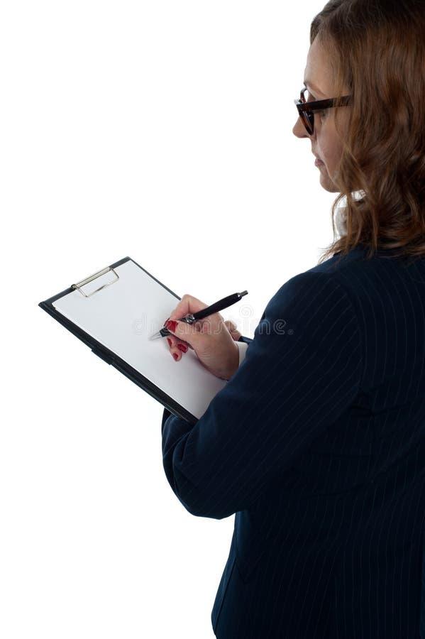 Dirija rellenar el impreso de la valoración de empleados imagenes de archivo