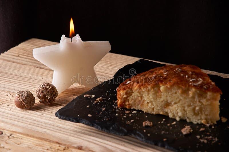 Dirija a torta de maçã cozida na placa do xisto e a tabela de madeira perto da vela sob a forma das estrelas fotografia de stock