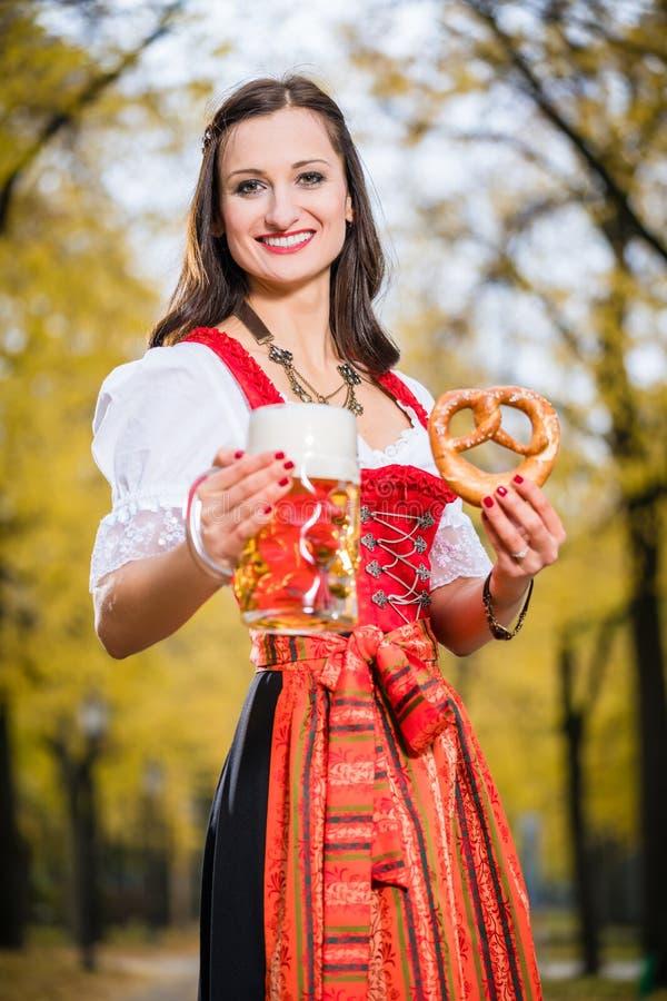 Dirndl девушки нося с кружкой кренделя и пива стоковое изображение