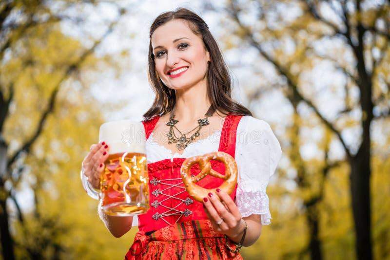 Dirndl vestindo da menina com a caneca do pretzel e de cerveja imagens de stock