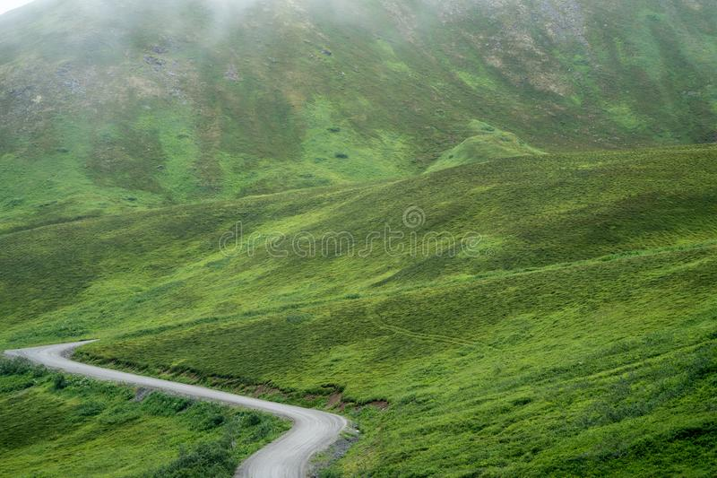 The dirt gravel road to Hatcher Pass, near Palmer Alaska and Ind. Ependence Mine on a foggy misty summer day royalty free stock photo
