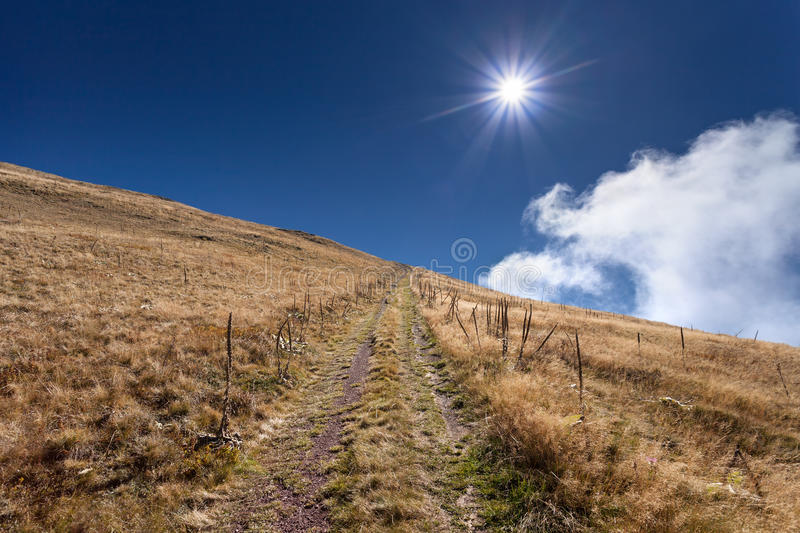 Dirt mountain road towards the sun royalty free stock image